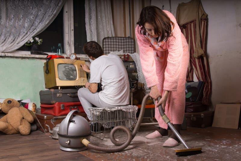 Pares jovenes que limpian un cuarto abandonado imagen de archivo