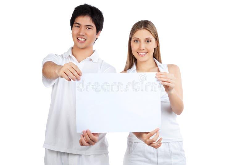 Pares jovenes que llevan a cabo el cartel en blanco fotos de archivo