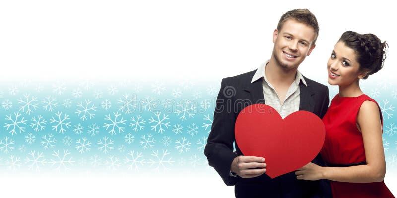 Pares jovenes que llevan a cabo el corazón sobre fondo del invierno imagen de archivo libre de regalías