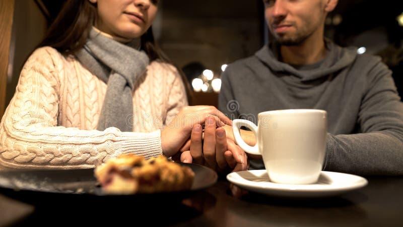 Pares jovenes que llevan a cabo las manos durante fecha rom?ntica en el caf?, disfrutando del tiempo junto fotos de archivo
