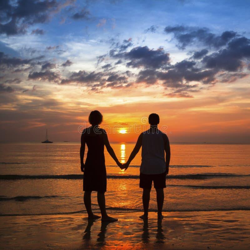Pares jovenes que llevan a cabo las manos en costa del océano durante la puesta del sol asombrosa imagen de archivo