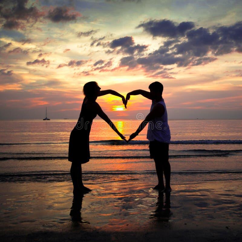 Pares jovenes que llevan a cabo las manos en forma de coraz?n en la puesta del sol imagen de archivo libre de regalías