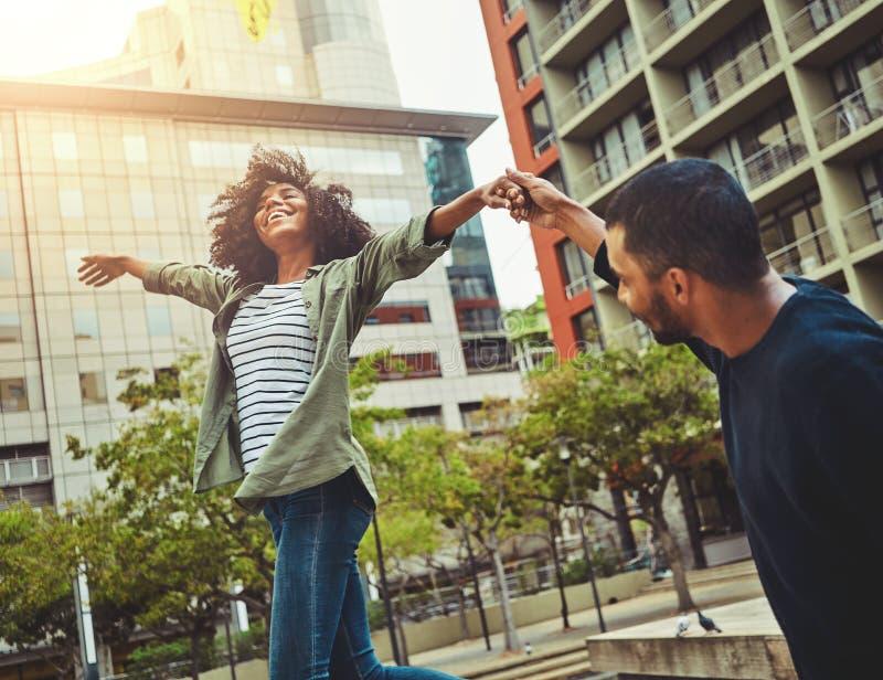 Pares jovenes que llevan a cabo las manos que gozan en la ciudad fotografía de archivo