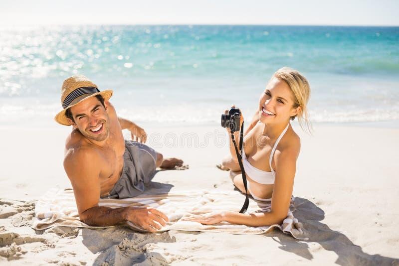 Pares jovenes que mienten en la playa foto de archivo