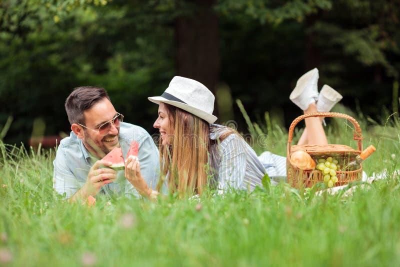 Pares jovenes que mienten en una manta de la comida campestre, comiendo el agua mellon y relaj?ndose imagen de archivo libre de regalías