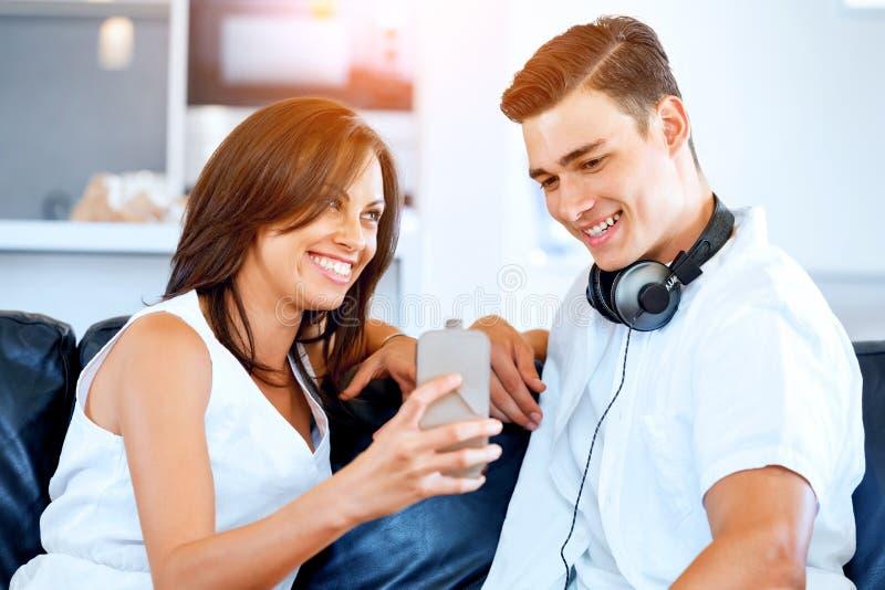Pares jovenes que miran el teléfono móvil mientras que se sienta en casa foto de archivo libre de regalías