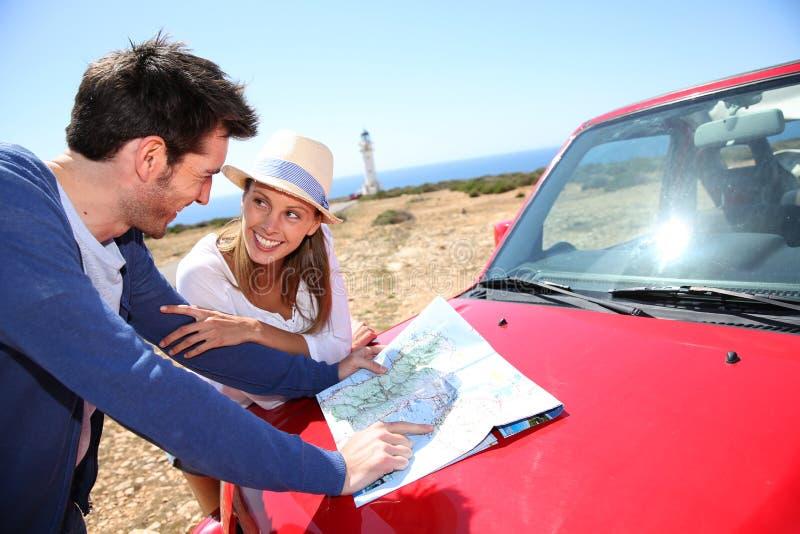 Pares jovenes que miran en mapa en un roadtrip imagen de archivo libre de regalías