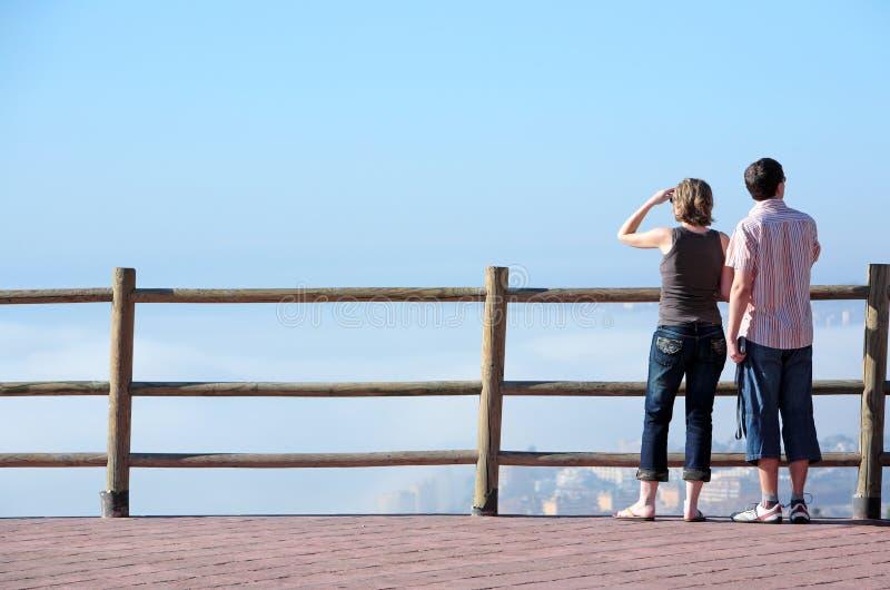 Pares jovenes que miran hacia fuera al mar del alto punto de vista fotografía de archivo