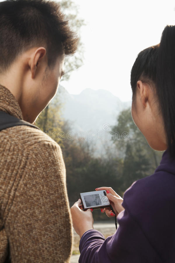 pares jovenes que miran la imagen en la pantalla de la cámara digital fotos de archivo