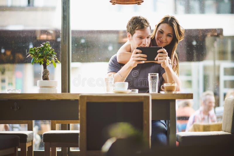 Pares jovenes que miran la tableta foto de archivo libre de regalías