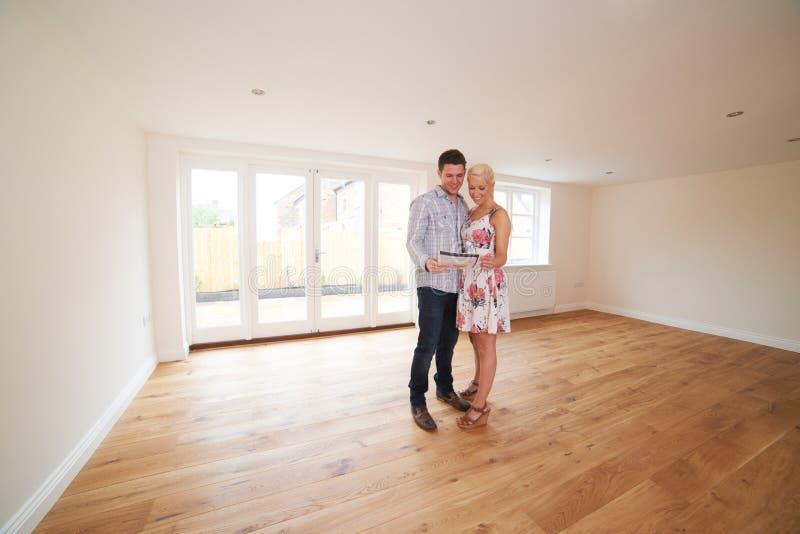 Pares jovenes que miran los detalles de la propiedad para el nuevo hogar imagen de archivo