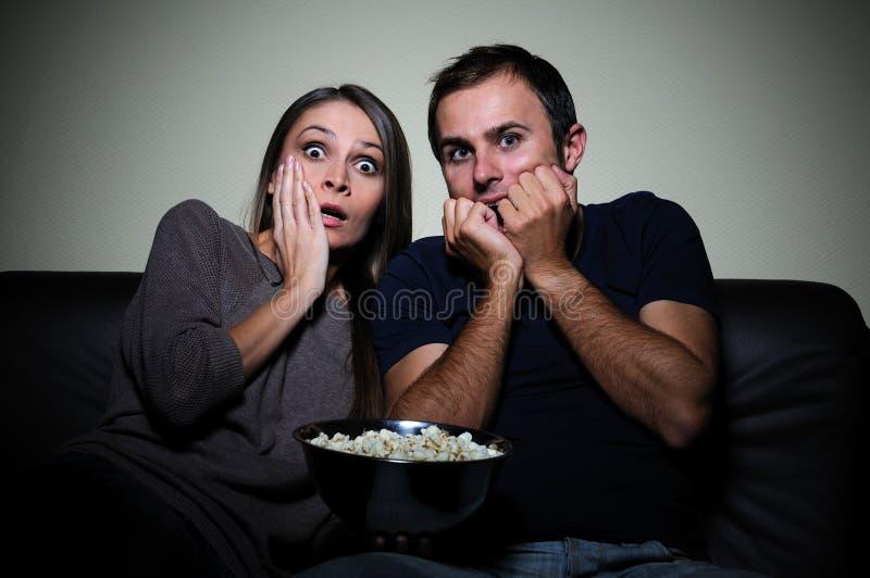 Pares jovenes que miran película asustadiza en la TV foto de archivo libre de regalías