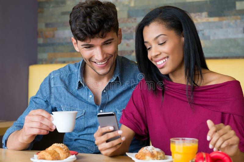 Pares jovenes que miran smartphone durante el desayuno fotografía de archivo libre de regalías
