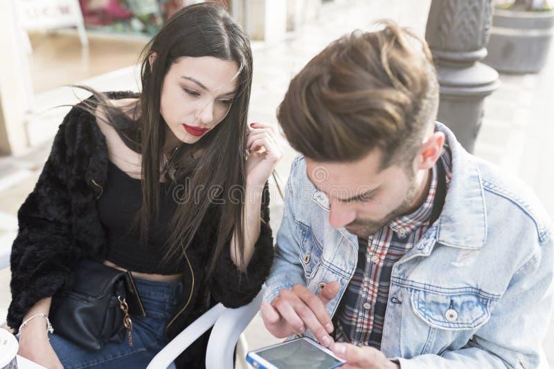 Pares jovenes que miran smartphone en terraza de la barra imagenes de archivo