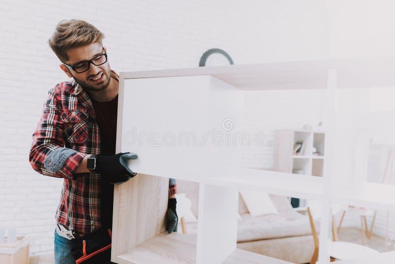 Pares jovenes que montan el estante de madera en casa imagen de archivo libre de regalías