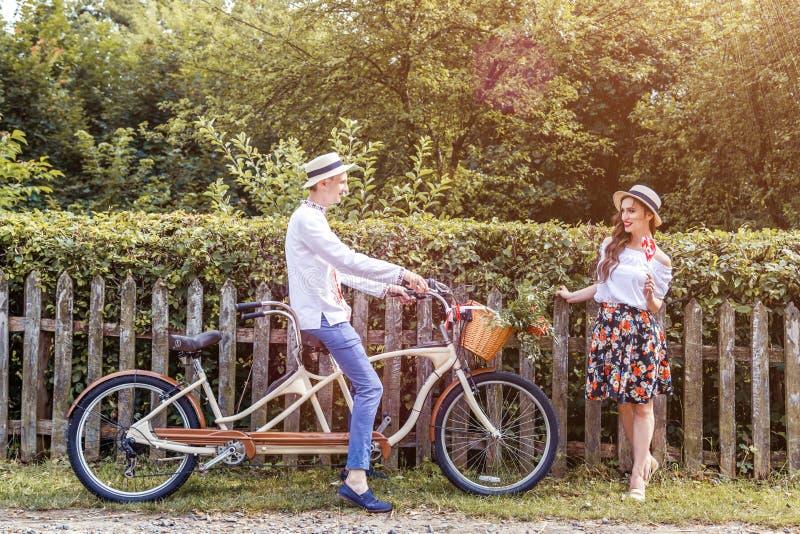 Pares jovenes que montan un tándem de la bici en el parque fotos de archivo libres de regalías