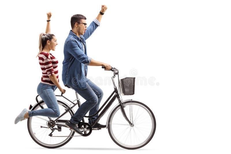 Pares jovenes que montan una bicicleta y que gesticulan felicidad foto de archivo
