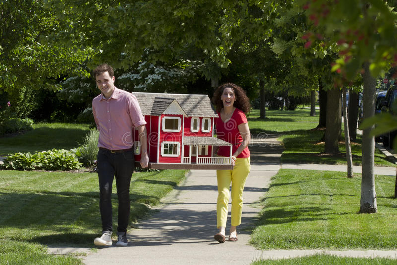 Pares jovenes que mueven una casa de muñecas foto de archivo libre de regalías