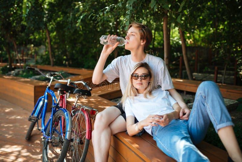 Pares jovenes que pasan tiempo en el banco de madera en parque con dos bicicletas cerca Muchacho que se sienta en banco y el agua fotografía de archivo libre de regalías