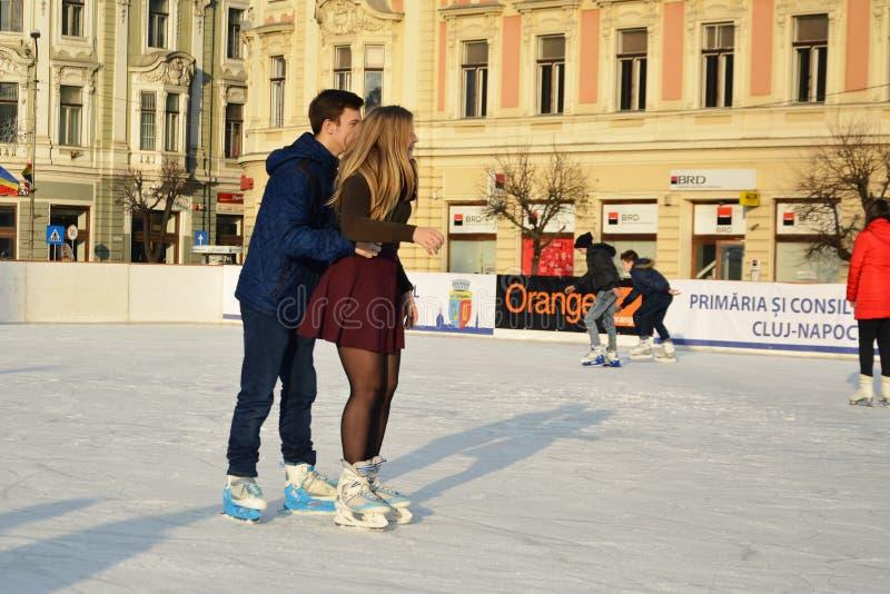 Pares jovenes que patinan en pista de patinaje de hielo imágenes de archivo libres de regalías