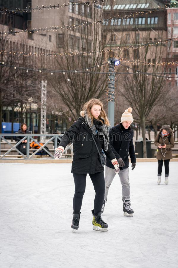 Pares jovenes que patinan en una pista de patinaje pública de hielo al aire libre en la ciudad foto de archivo