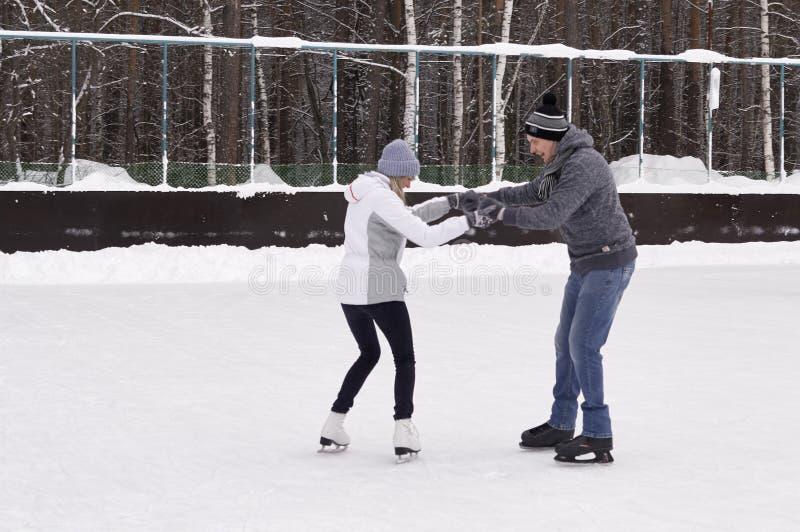 Pares jovenes que patinan en una pista de patinaje p?blica de hielo al aire libre en la ciudad foto de archivo libre de regalías
