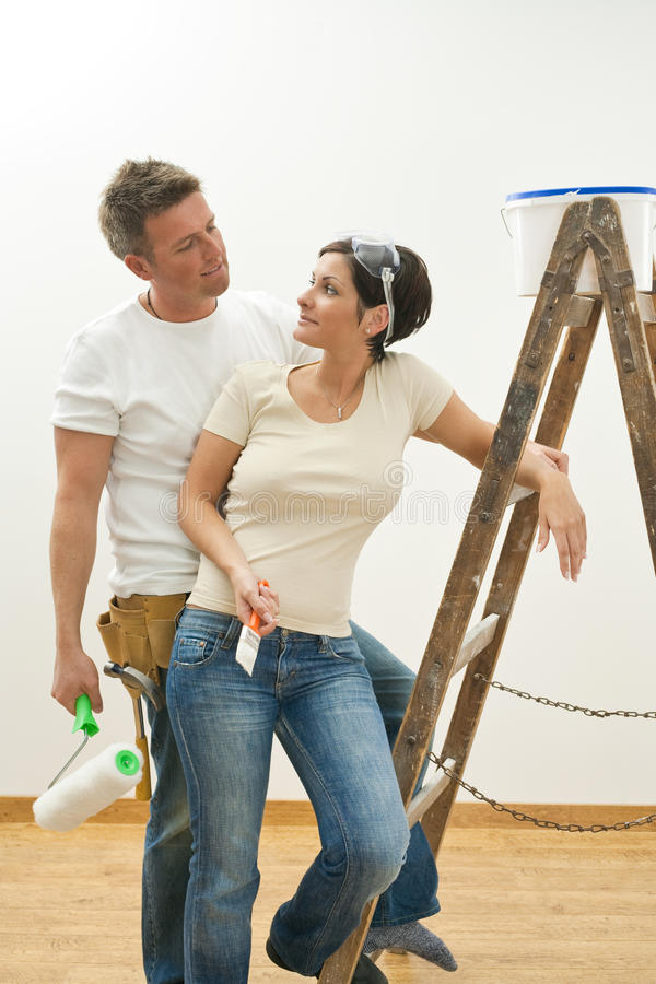 Pares jovenes que pintan el nuevo hogar imagen de archivo