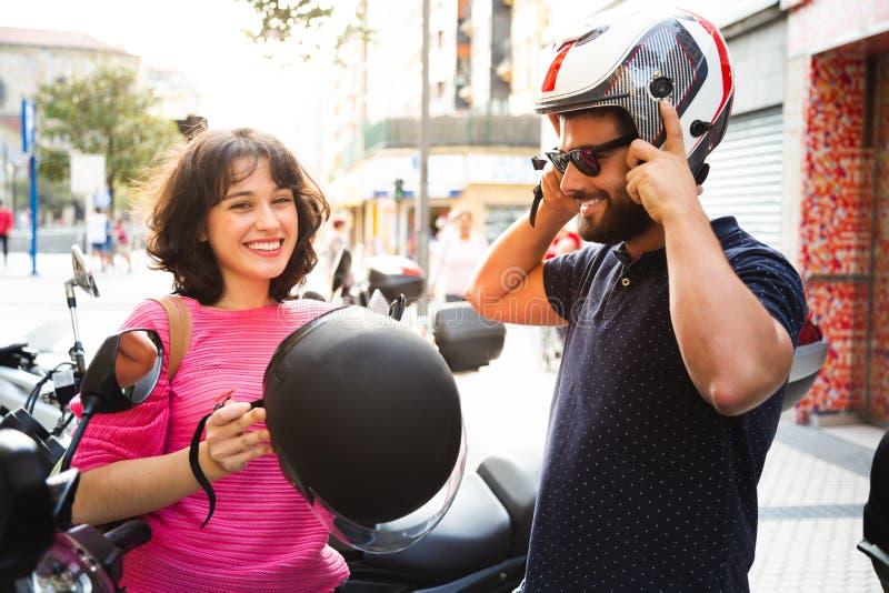 Pares jovenes que ponen en casco para montar una motocicleta fotos de archivo