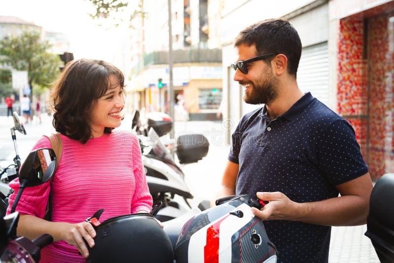 Pares jovenes que ponen en casco para montar una motocicleta imágenes de archivo libres de regalías