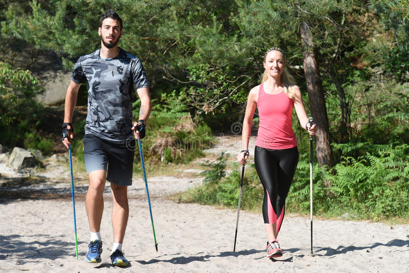 Pares jovenes que practican el paseo nórdico del ` s fotografía de archivo