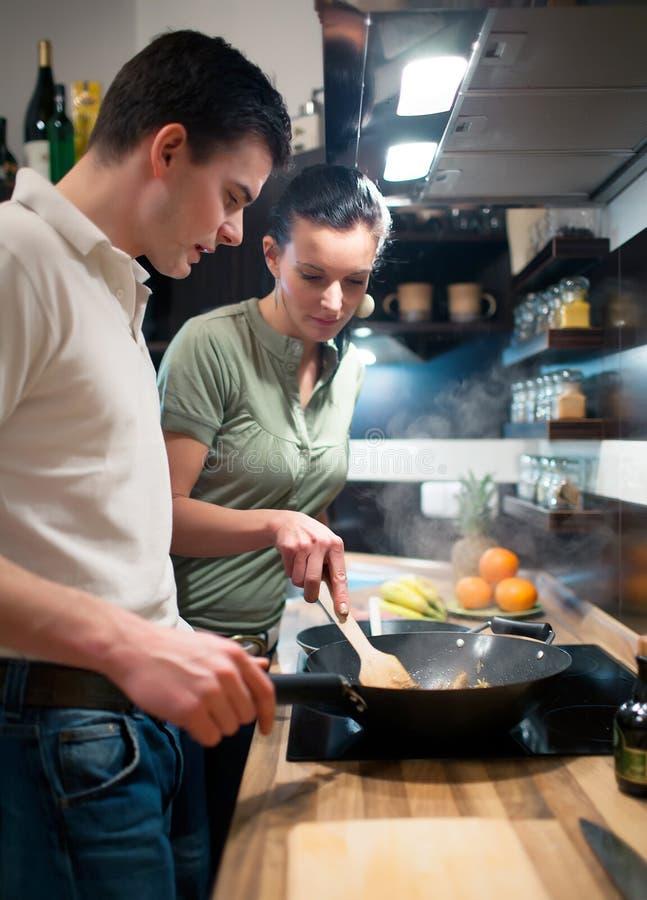 Pares jovenes que preparan el almuerzo en cocina foto de archivo