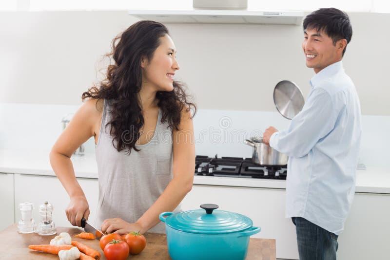 Pares jovenes que preparan la comida junta en cocina imagenes de archivo