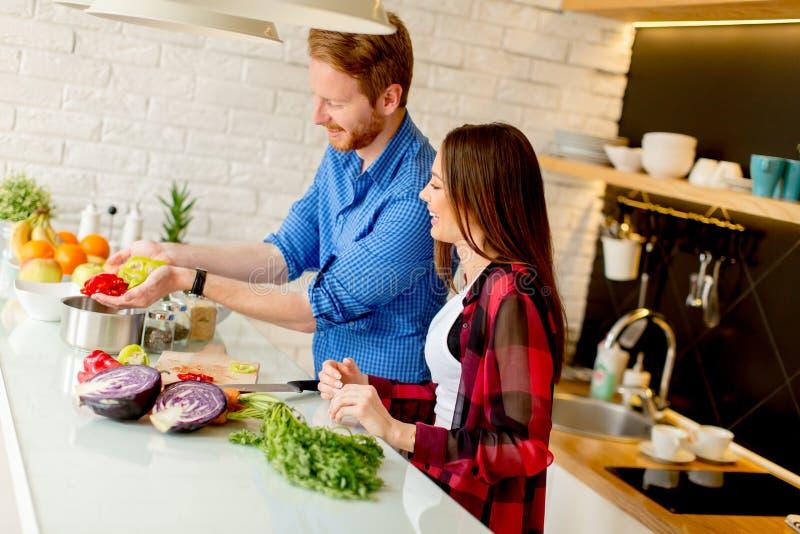 Pares jovenes que preparan la comida sana en la cocina fotografía de archivo libre de regalías