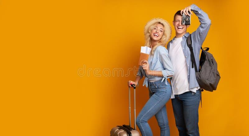 Pares jovenes que presentan con los boletos y la cámara sobre fondo amarillo fotografía de archivo libre de regalías
