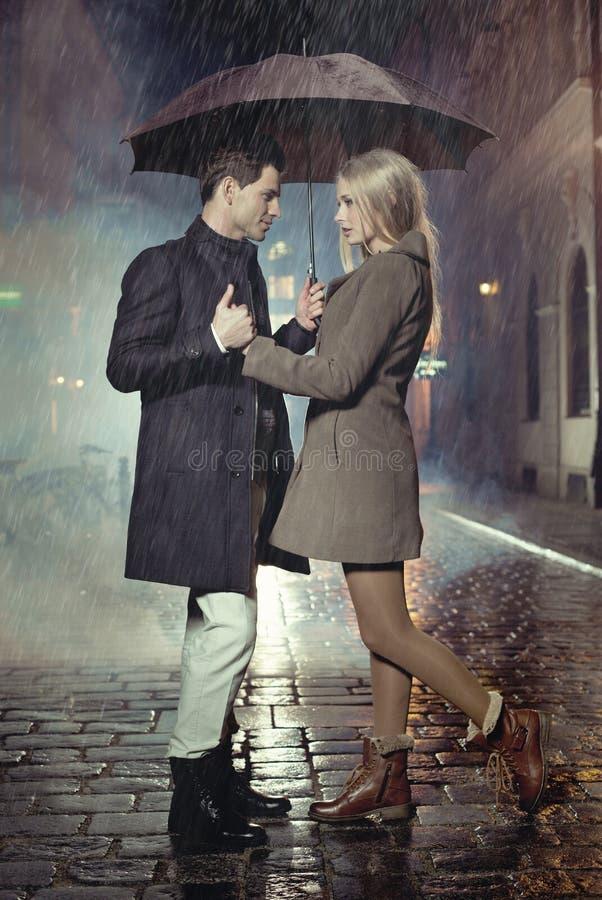 Pares jovenes que presentan en fuertes lluvias foto de archivo