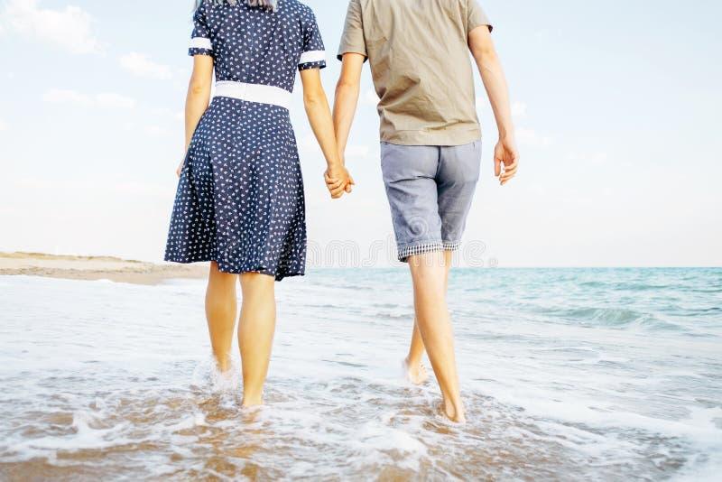 Pares jovenes que recorren en la playa fotografía de archivo