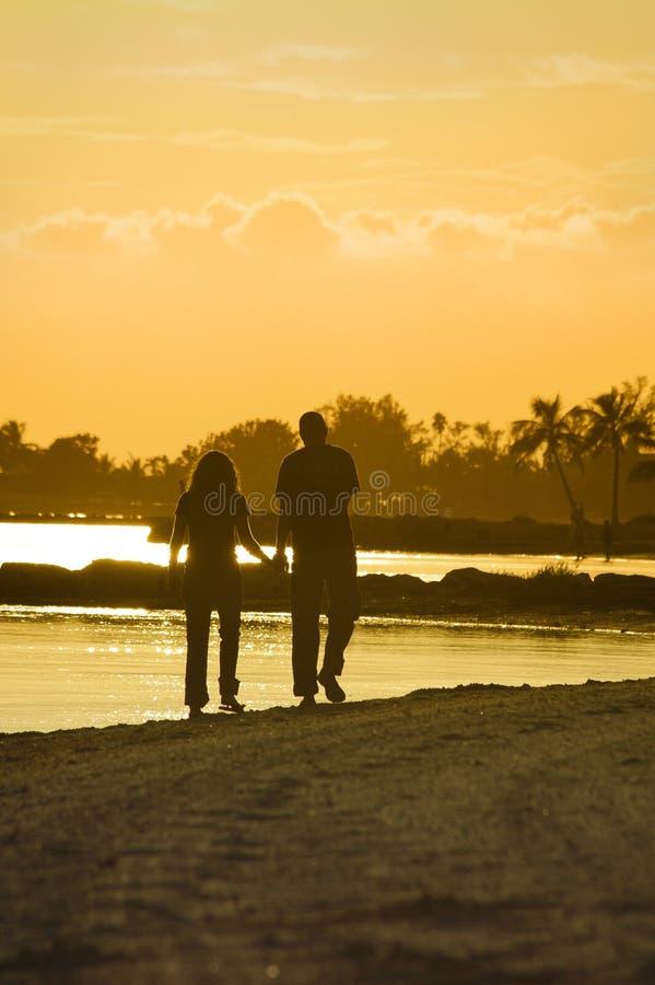 Pares jovenes que recorren en la playa en la puesta del sol fotografía de archivo libre de regalías