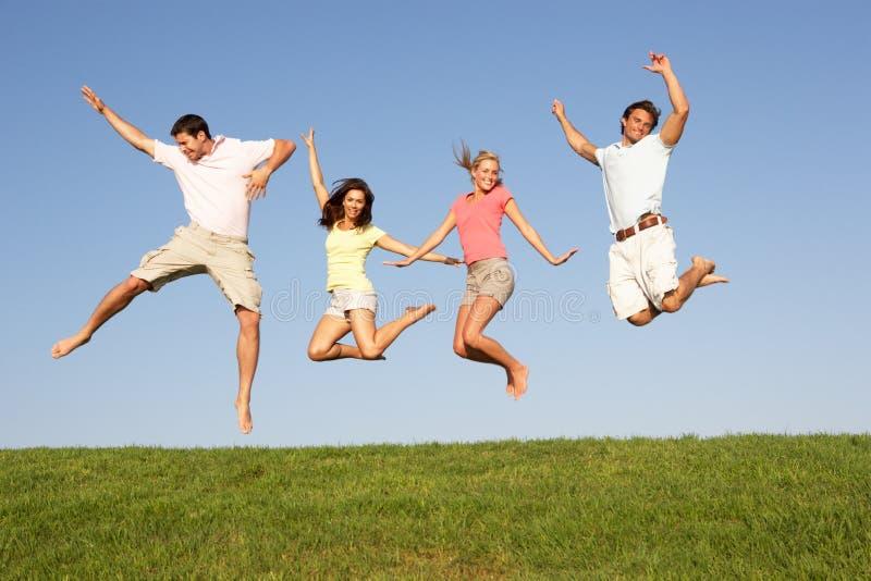 Pares jovenes que saltan en aire