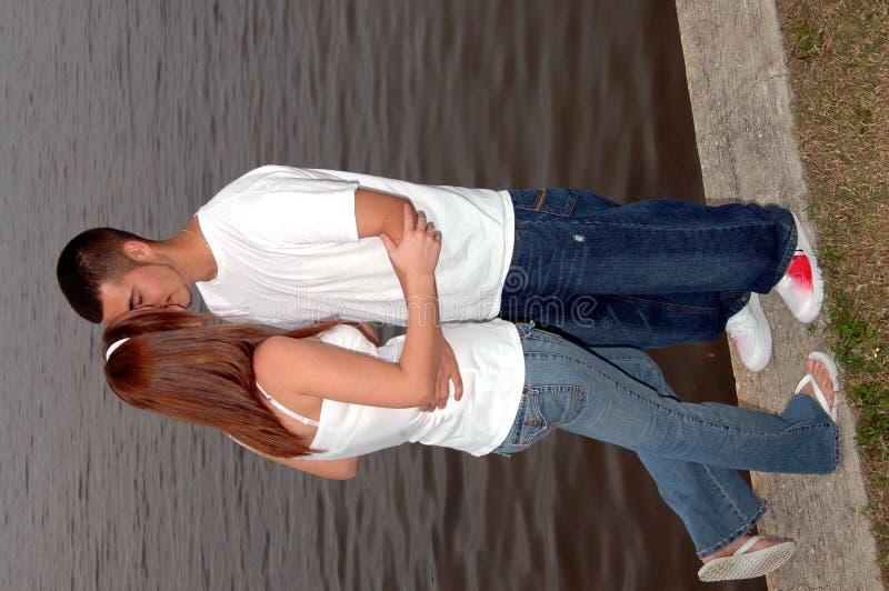 Pares jovenes que se besan al aire libre imagen de archivo