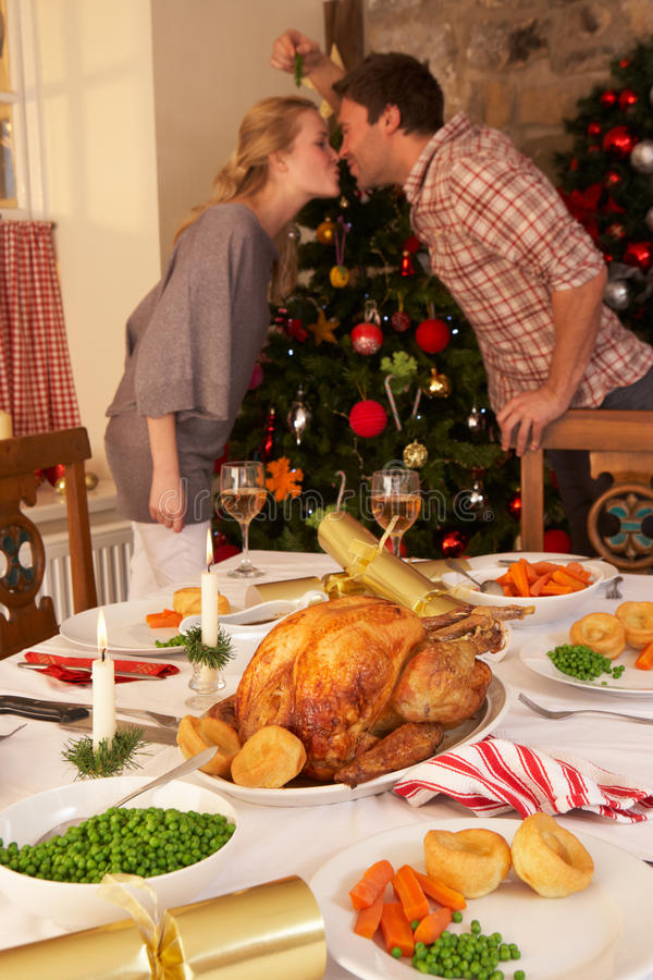 Pares jovenes que se besan bajo muérdago en la Navidad foto de archivo