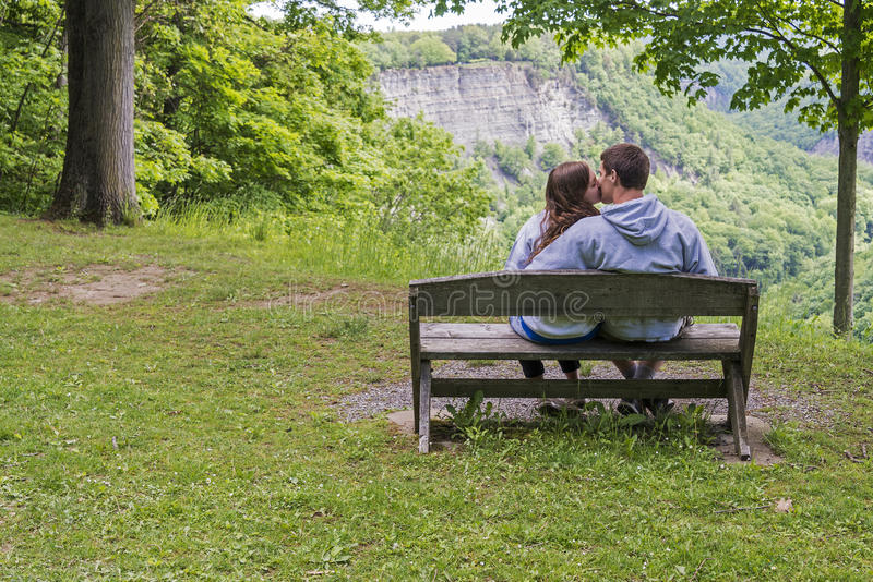 Pares jovenes que se besan en el parque imagen de archivo