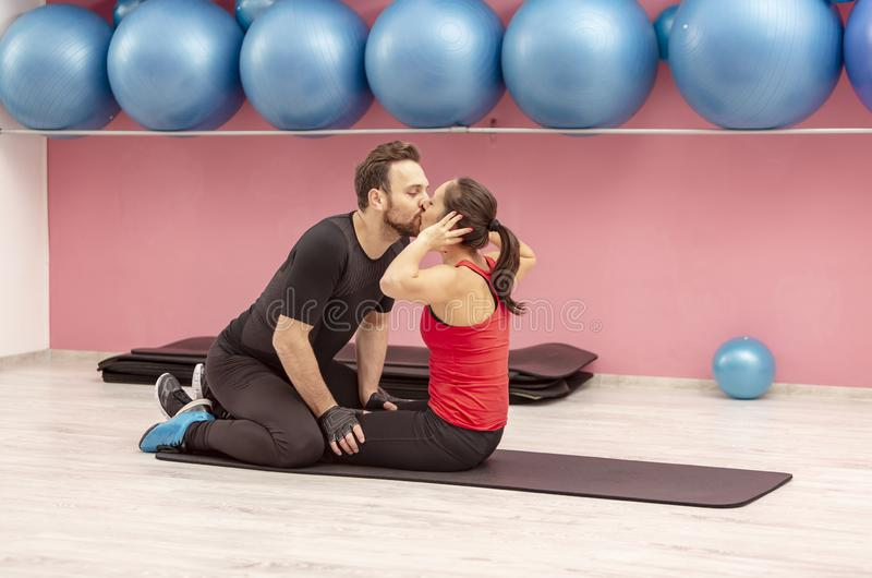 Pares jovenes que se besan en un gimnasio imagenes de archivo