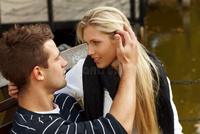 Pares jovenes que se besan por el lago fotos de archivo