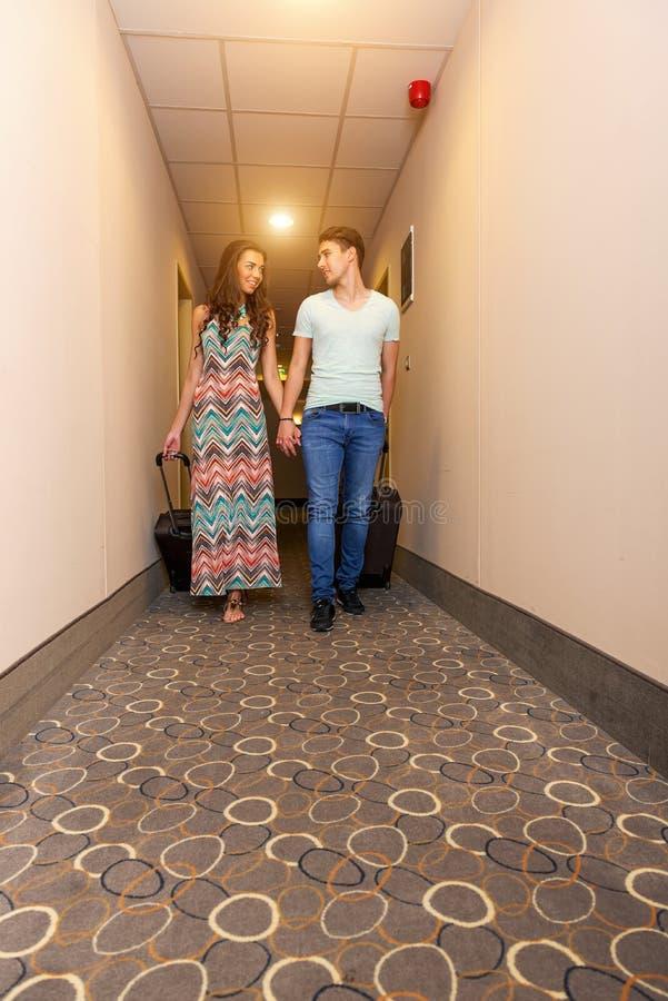 Pares jovenes que se colocan en el pasillo del hotel sobre llegada, buscando el sitio, sosteniendo las maletas fotos de archivo libres de regalías