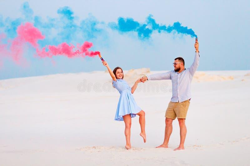 Pares jovenes que se colocan en una arena y que sostienen la bomba de humo coloreado, pares románticos con color azul y bomba de  fotos de archivo libres de regalías