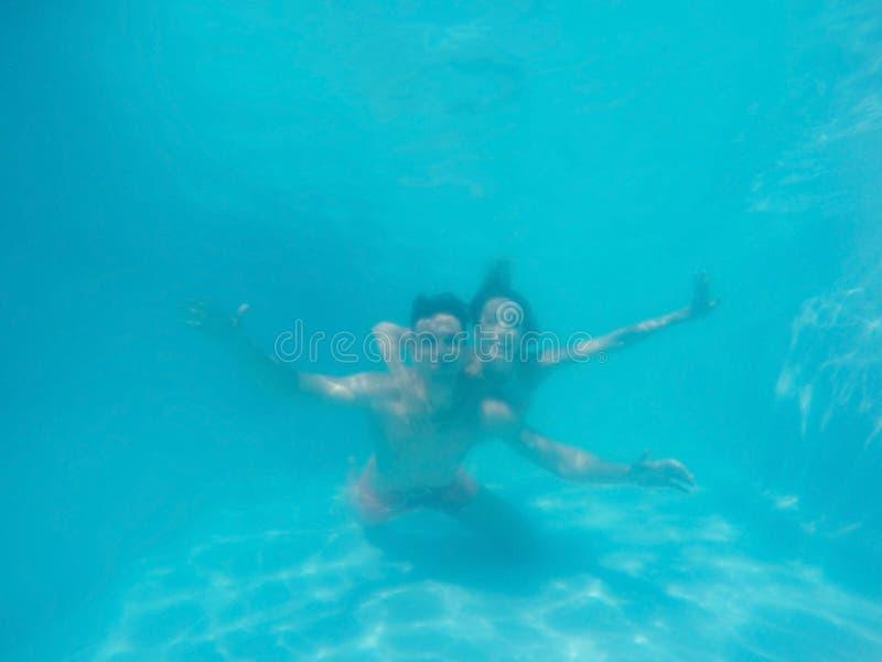 Pares jovenes que se divierten bajo el agua foto de archivo