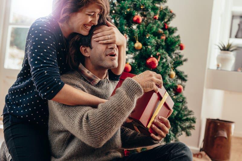 Pares jovenes que se divierten que celebra la Navidad con los regalos fotografía de archivo