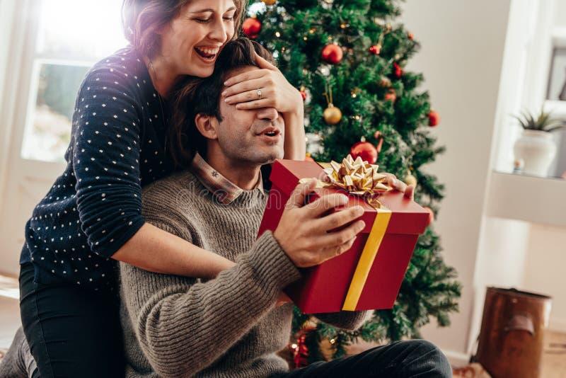 Pares jovenes que se divierten que celebra la Navidad con los regalos imagen de archivo