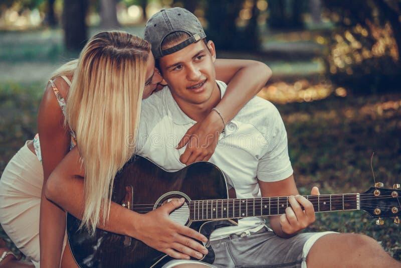 Pares jovenes que se divierten con la guitarra durante comida campestre en el parque imagenes de archivo