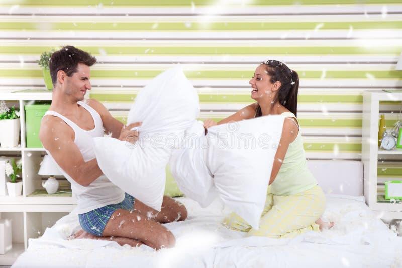 Pares jovenes que se divierten con las almohadas en casa foto de archivo libre de regalías